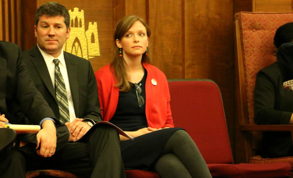 A man, left, and a woman, right, sit in red chairs.