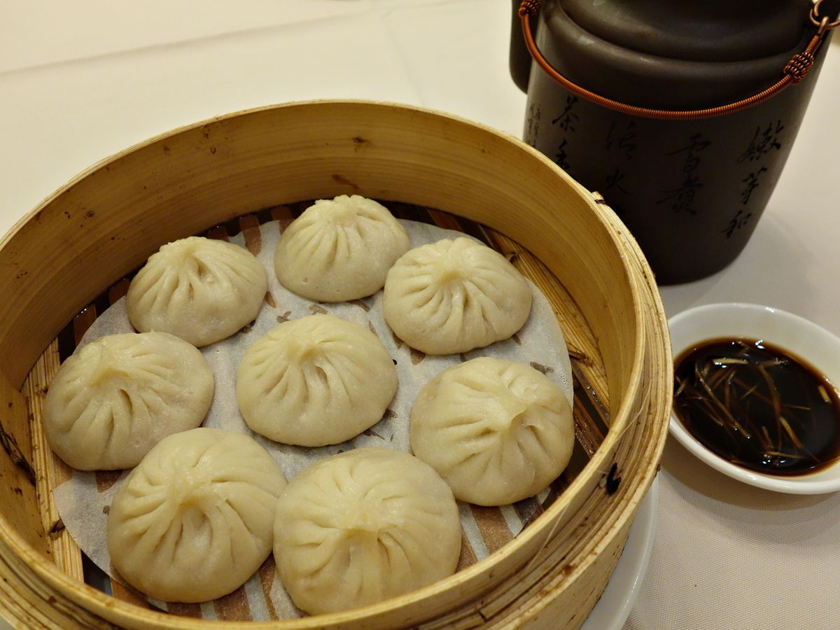 A steamer basket full of juicy soup dumplings, beside a small dish of dipping sauce