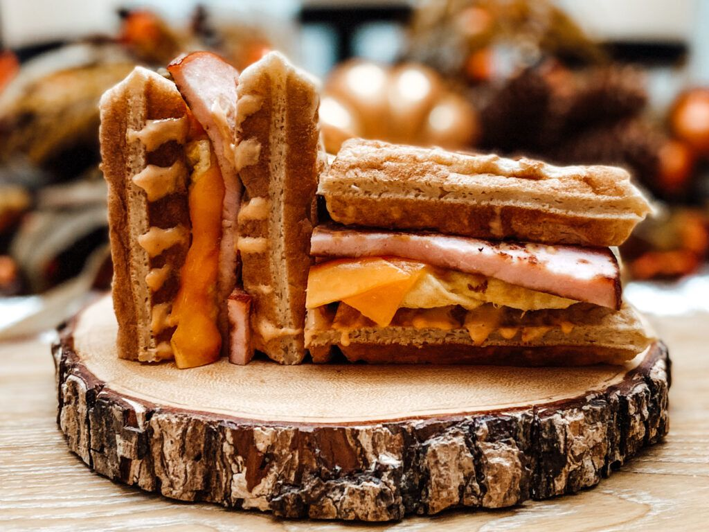 A waffle sandwich has one half laying down and one half on end, stuffed with ham and cheese, on a log slice for a plate