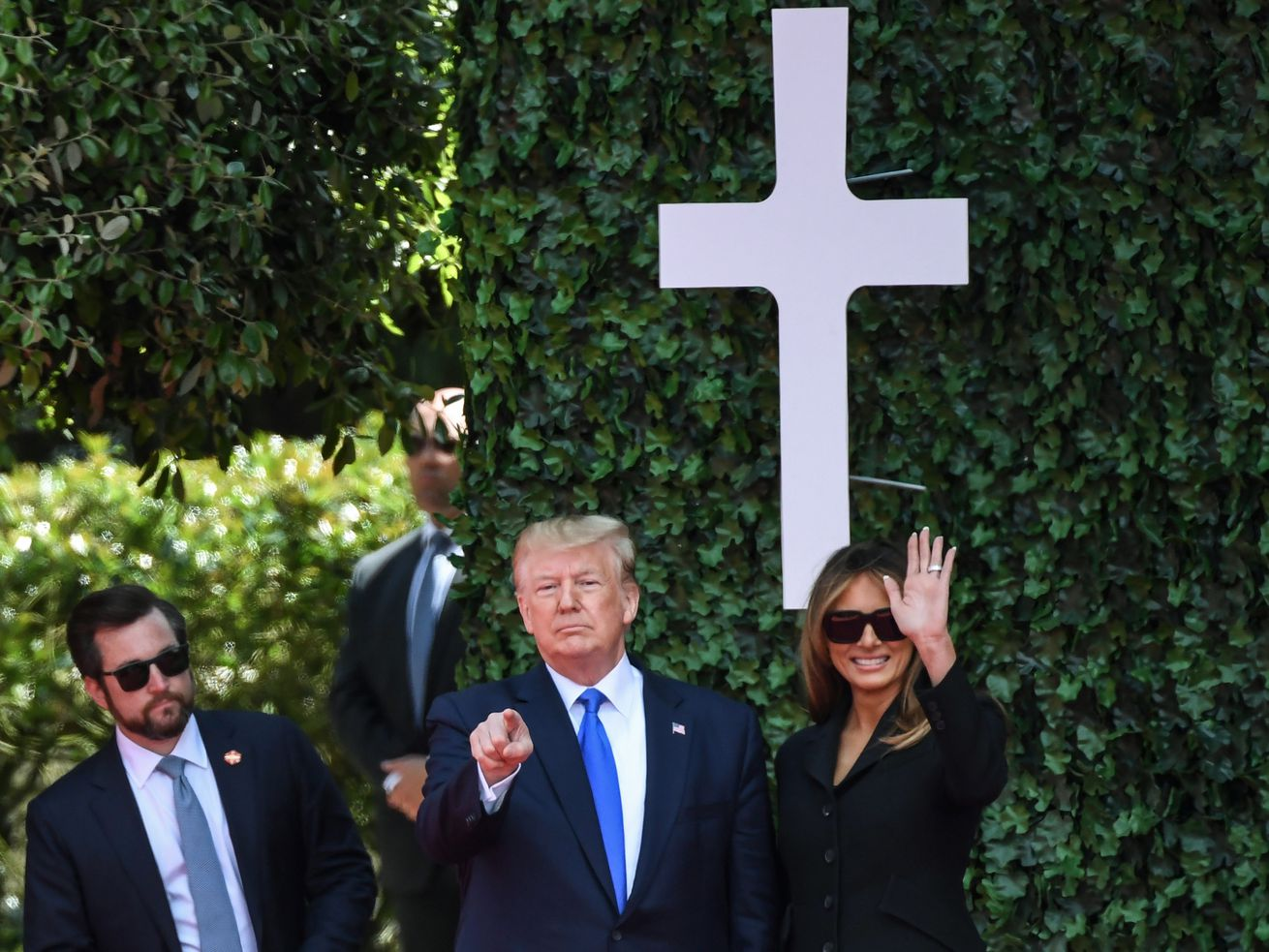 President Donald Trump (C) and first lady Melania Trump attend a ceremony at the Normandy American Cemetery and Memorial in Normandy, France, on June 6, 2019.