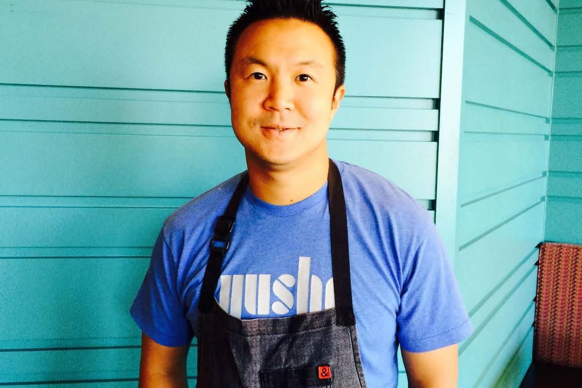 A chef wears a blue T-shirt and a black apron
