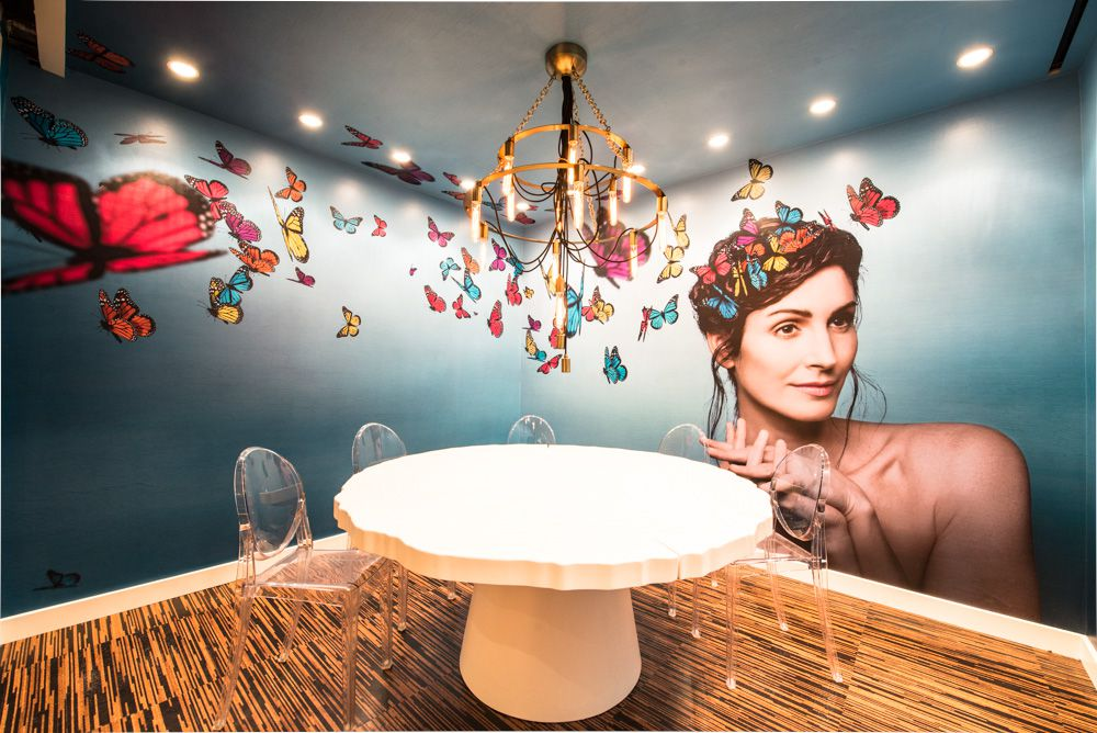 Oyamel's private diing room featuring a mural with colorful butterflies and a woman on the wall.