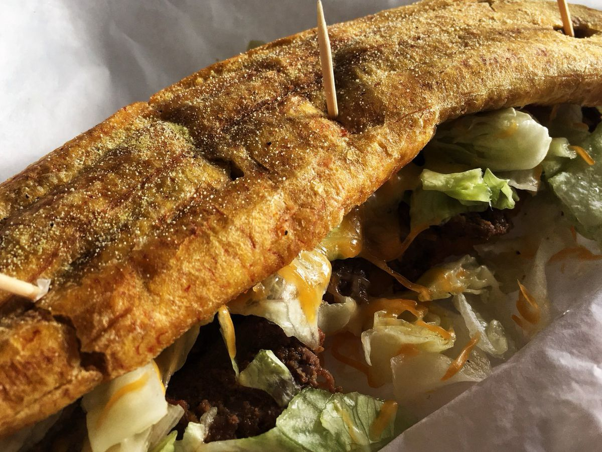 A sandwich with plantains instead of bread is held together with toothpicks and has meat, cheese, and lettuce overflowing from the sides.