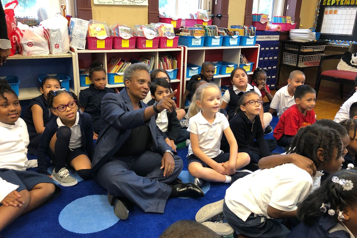 Chicago Mayor Lori Lightfoot sits with students on the first day of school at Salazar Elementary Bilingual Center. If teachers walk out this fall, some 361,000 Chicago students would be affected.