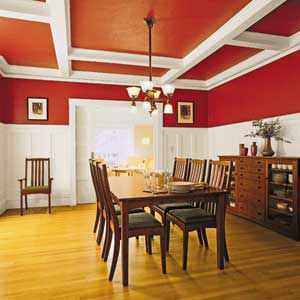 Kitchen with white wainscot, brown dining table, and interior walls and ceilings both painted red.