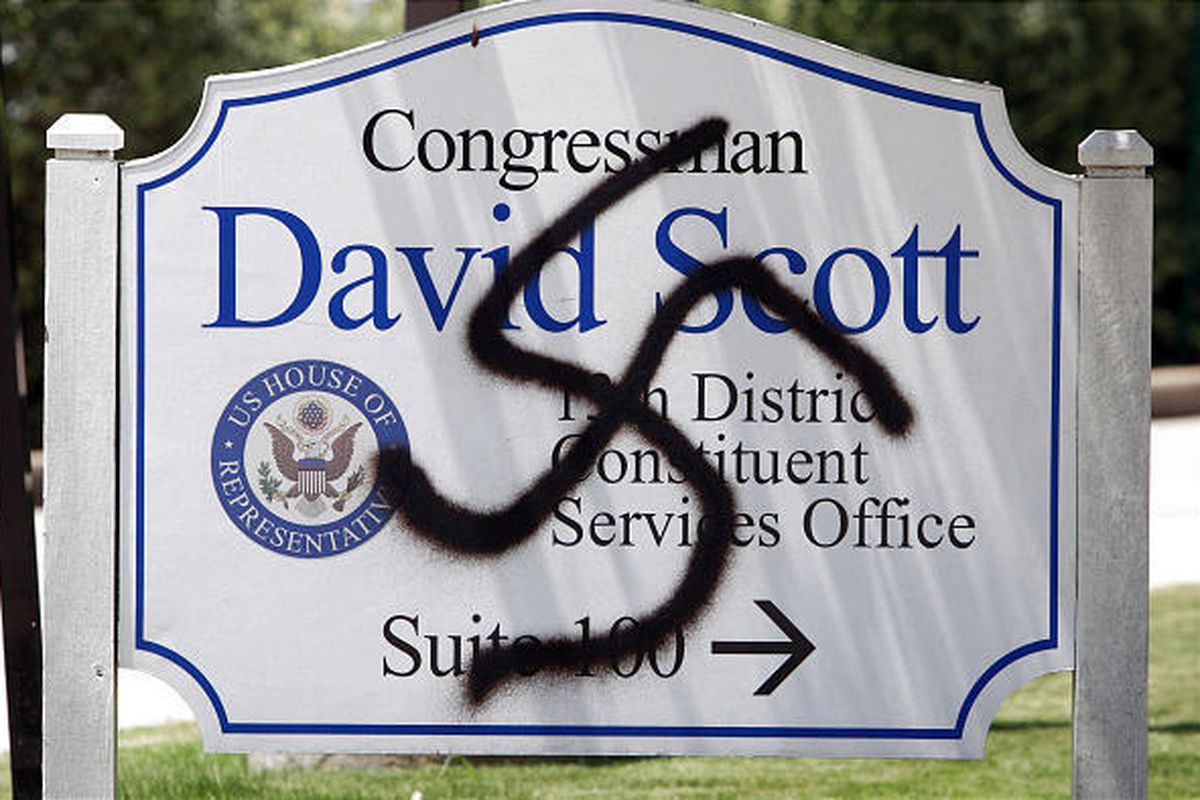 A vandalized sign stands outside a congressman's office in Smyrna, Ga. Are such incidents evidence of some new political virulence?