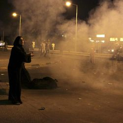 """A Bahraini woman shouts at riot police, unseen, to stop firing as residents help those who fell during the barrage of tear gas and stun grenades aimed at dispersing villagers gathered in Sadad, Bahrain, early Saturday, Sept. 29, 2012, at the scene where a youth was killed, allegedly by police shotgun fire. An Interior Ministry statement said a police patrol was attacked with petrol bombs and iron rods late Friday, and one person died when """"policemen defended themselves."""" A witness among protesters said demonstrators were marching against the government when a policeman suddenly stepped out near the youth and shot him at close range."""