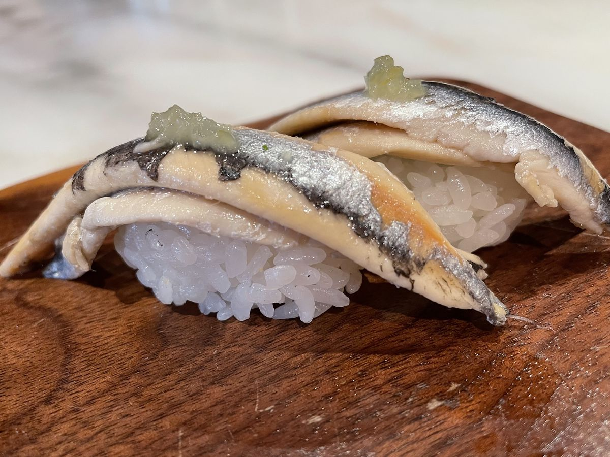 Two pieces of cured white anchovy sushi