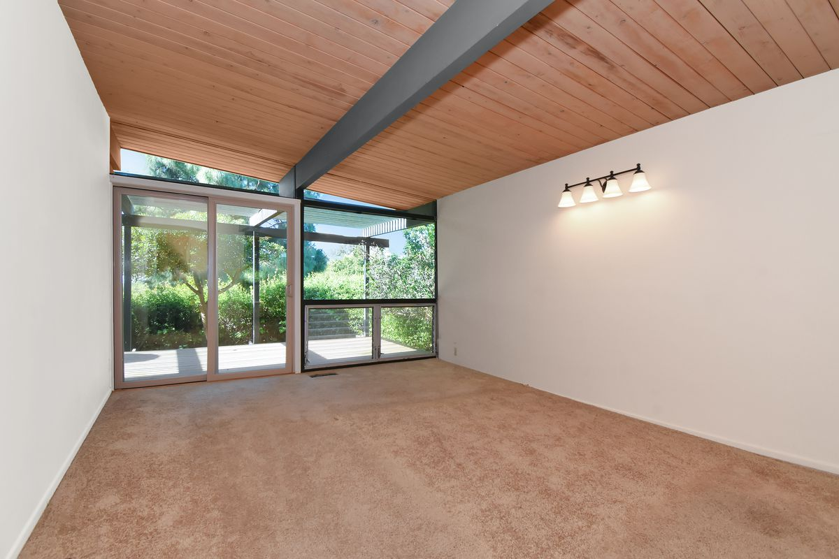 A room with carpeted floors and white walls. Trees and vegetation can be seen through glass doors at the far end of the room