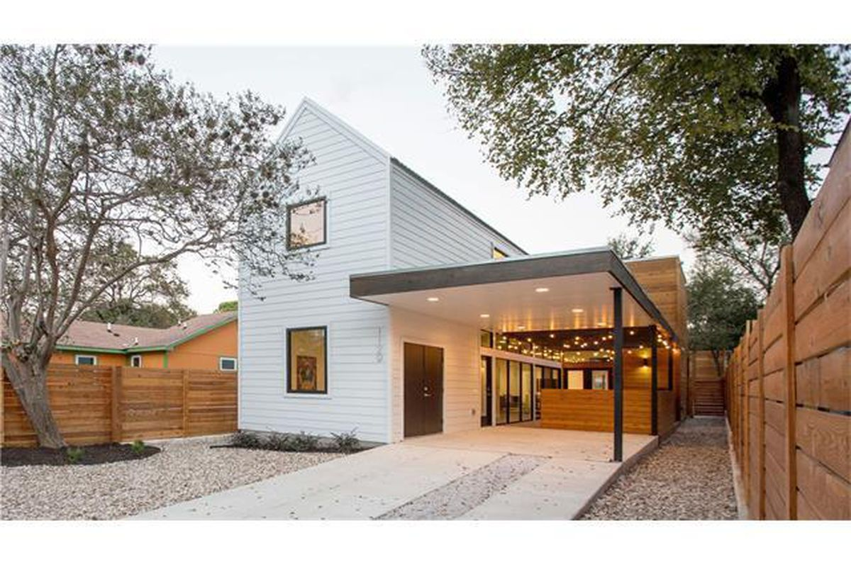 Mod farmhouse, white, two-story, with long, flat carport roof on side that covers patio and part of driveway