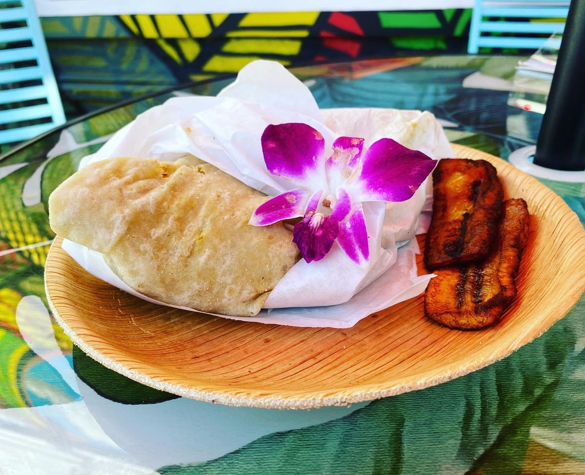 Roti wrap on a wooden plate, garnished with a purple flower