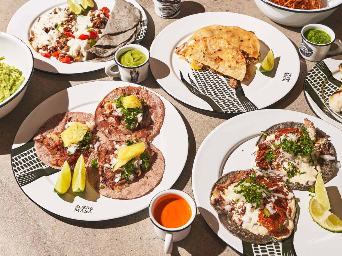 An assortment of tortilla dishes, including tacos and gringas, topped with meats and cheeses.