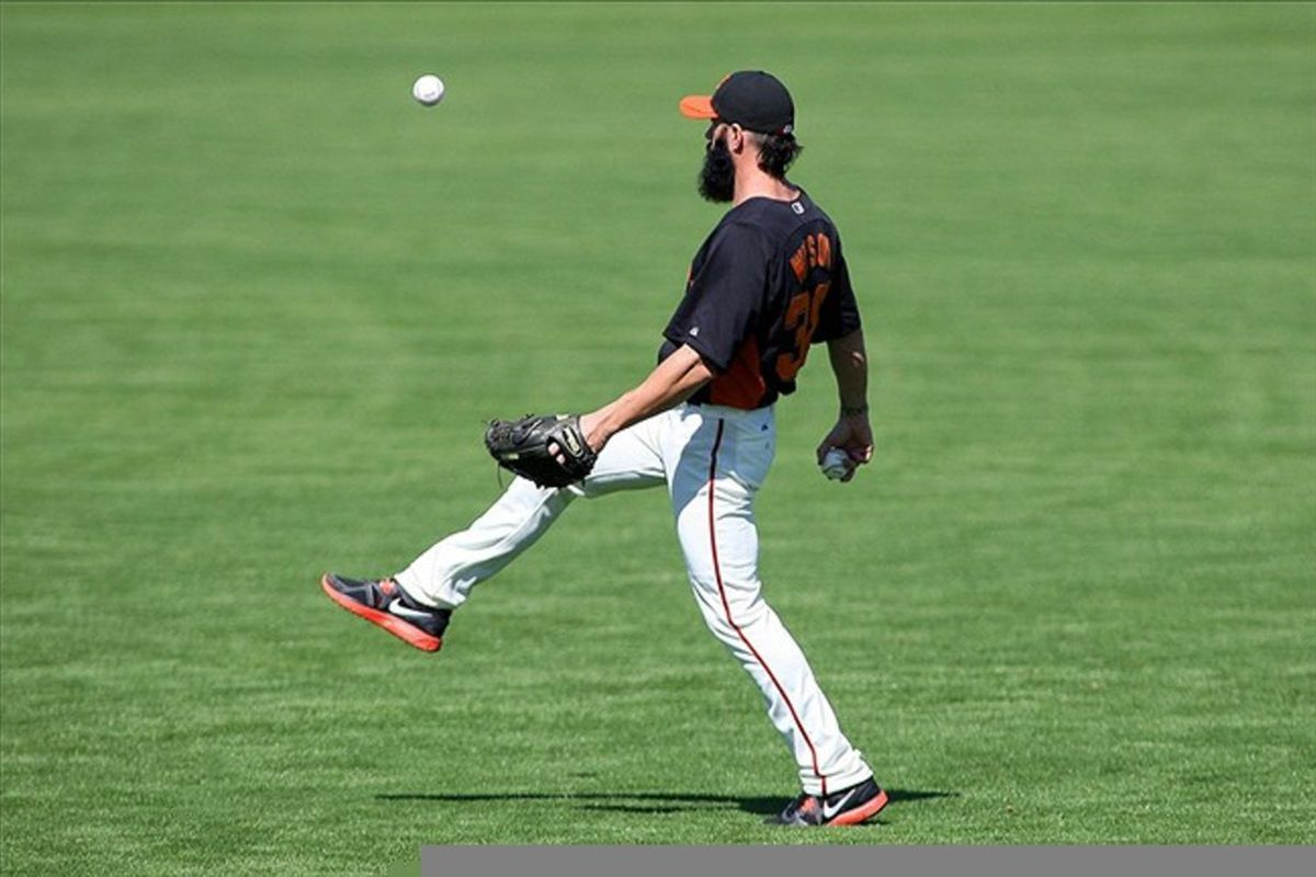 Mar 13, 2012; Scottsdale, AZ, USA; San Francisco Giants relief pitcher Brian Wilson (38) kicks a baseball in the air during batting practice before a game against the Chicago Cubs at Scottsdale Stadium.  Mandatory Credit: Jake Roth-US PRESSWIRE