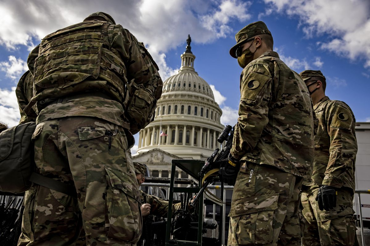 Men in green fatigues check in with a burly man in bulletproof military vest, and are being given assault rifles. Behind them looms the white dome of the Capitol building, rising up behind tall black fences.