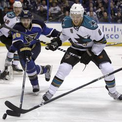 St. Louis Blues' Carlo Colaiacovo, left, and San Jose Sharks' Joe Pavelski reach for a loose puck during the first period in Game 2 of an NHL Stanley Cup first-round hockey playoff series Saturday, April 14, 2012, in St. Louis.