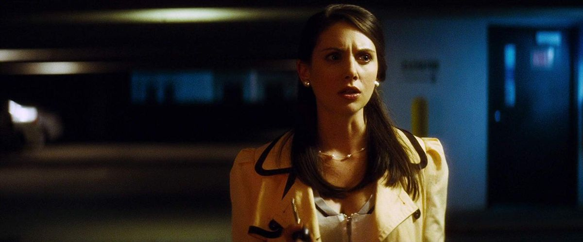 rebecca walters (alison brie) stands in a yellow blazer, scared in the middle of a shadowy parking garage