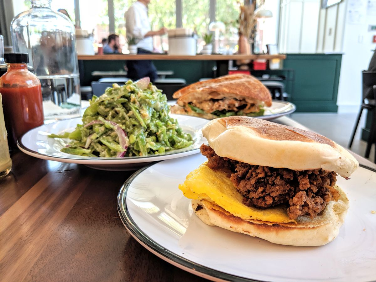 A fried chicken sandwich served on a Portuguese bun is in the foreground of the photo, with a stacked-high sugar snap pea salad and a roasted cauliflower sandwich in the background. Shot at Shy Bird in Cambridge.