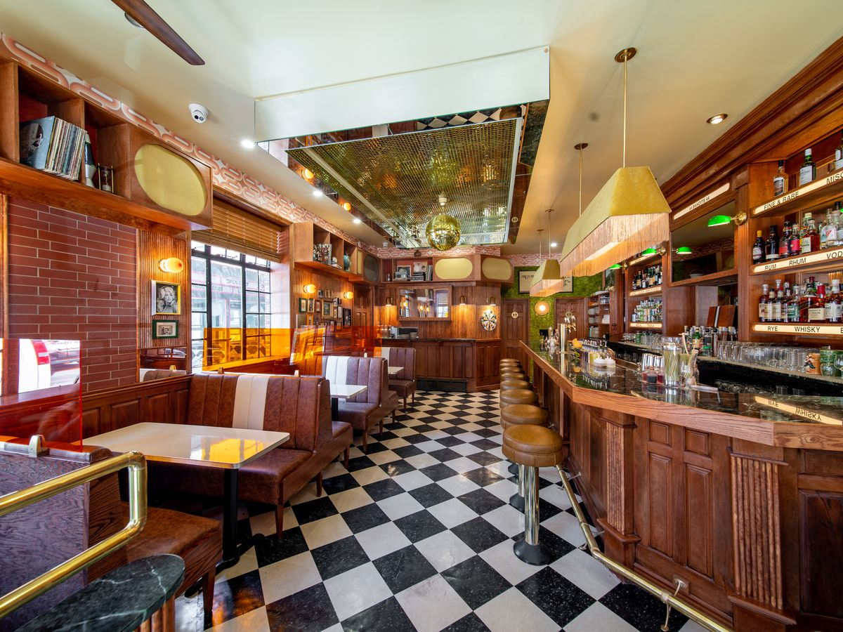 The inside of a diner with wood paneled walls and a bar, black and white checkered floor, and dark brown leather booths with white tables.