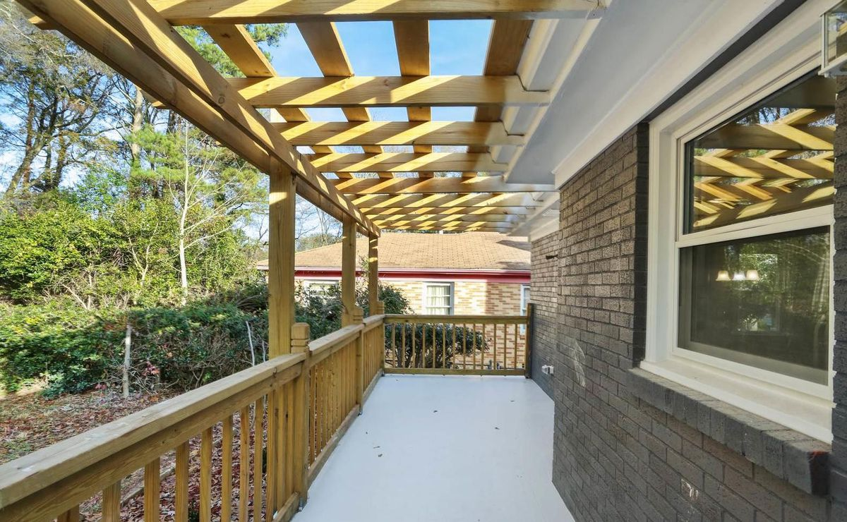 Patio on back of house with pergola extending from the roof.