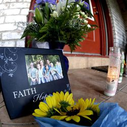 A photograph, flowers and candles are left on the porch where a fatal home shooting took place Thursday, July 10, 2014, in Spring, Texas. The Harris County Sheriffs Office says Ronald Lee Haskell was booked Thursday on a capital murder/multiple murders charge and held without bond. Authorities believe Haskell fatally shot two adults and four children on Wednesday night and critically wounded a 15-year-old girl, who called 911.