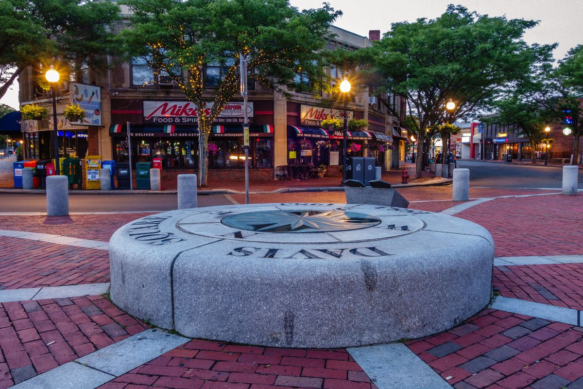A raised circular stone in an open plaza.