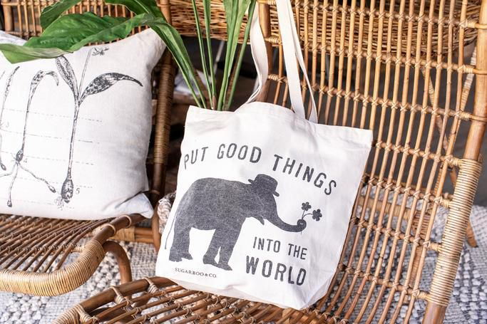 A pillow and a tote are seen on wicker furniture on a rug.