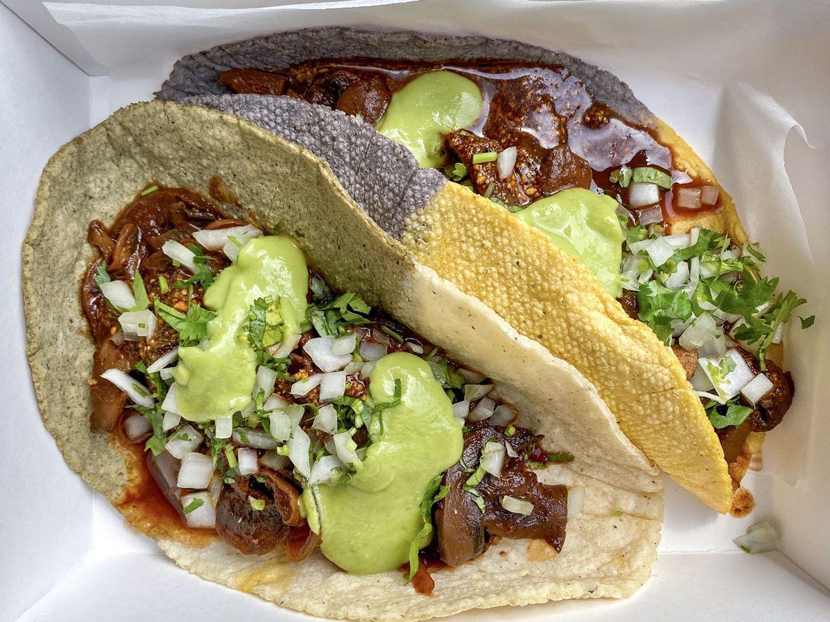 A photo of Republica's vegan mushroom adobo tacos served with avocado, onion, and cilantro