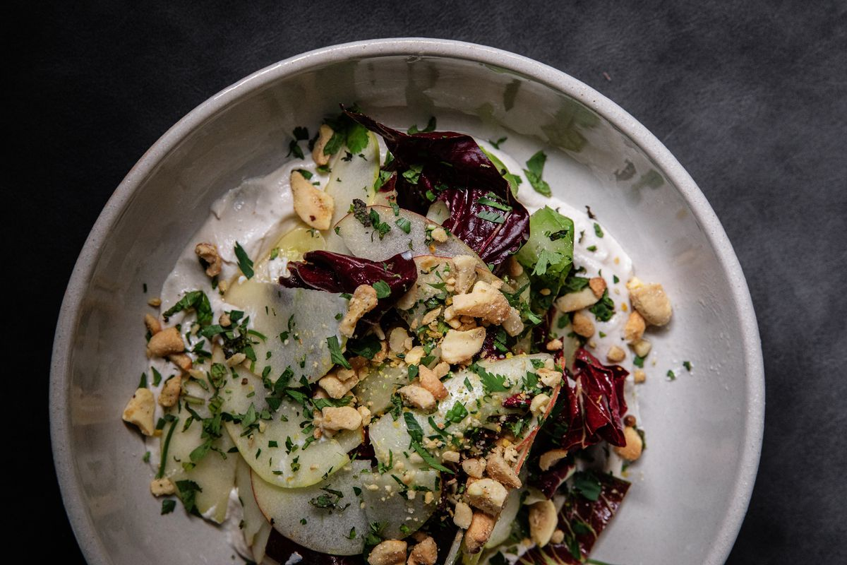 A circular plate with thinly sliced vegetables, crumbled cashews, and red pieces of what looks like radicchio.
