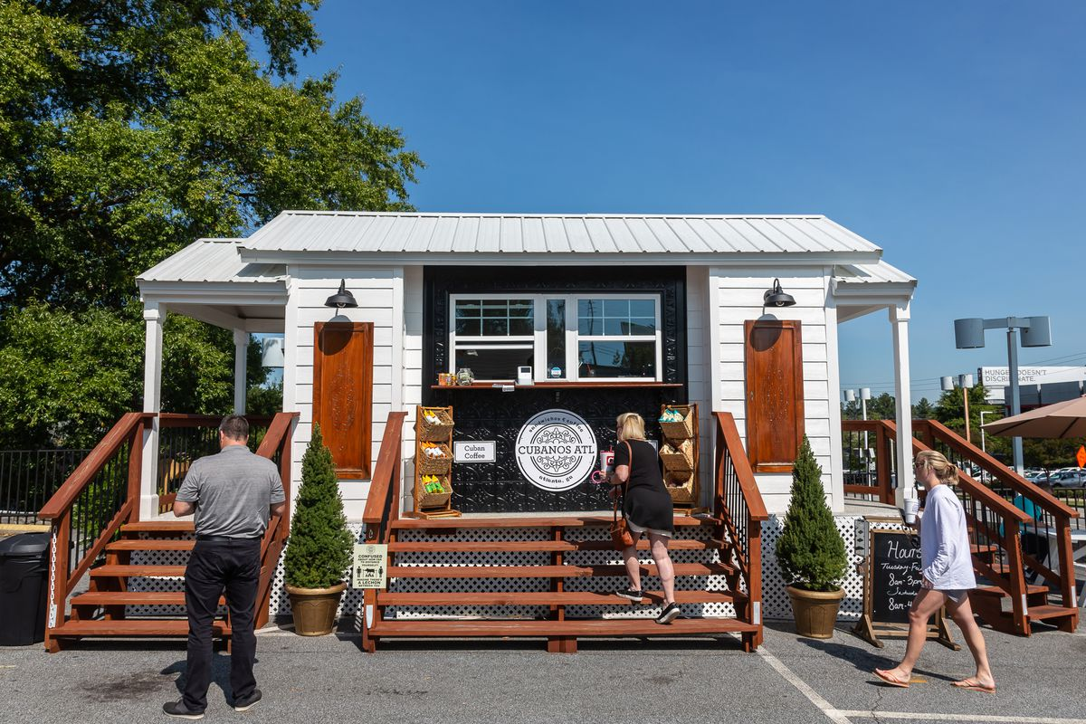 A white tiny house with two to-go windows framed in black paint with people standing in front of it masked waiting to get their takeout orders