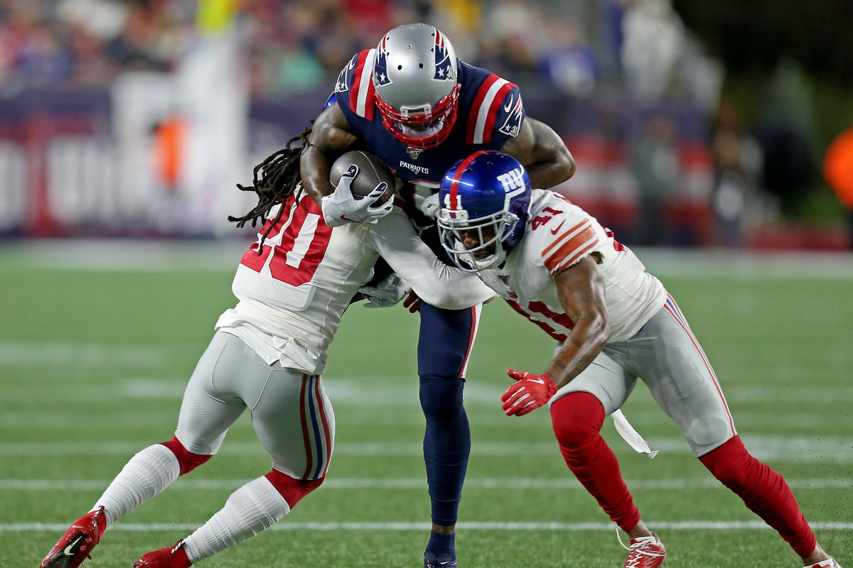 Josh Gordon of the New England Patriots is hit by Janoris Jenkins of the New York Giants and Antoine Bethea of the New York Giants as the Patriots take on the Giants at Gillette Stadium on October 10, 2019 in Manchester, NH.