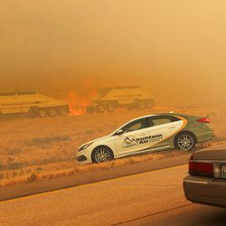 Cars and trucks turn around on I-84 as fire burns along the freeway near Weber Canyon on Tuesday, Sept. 5, 2017.