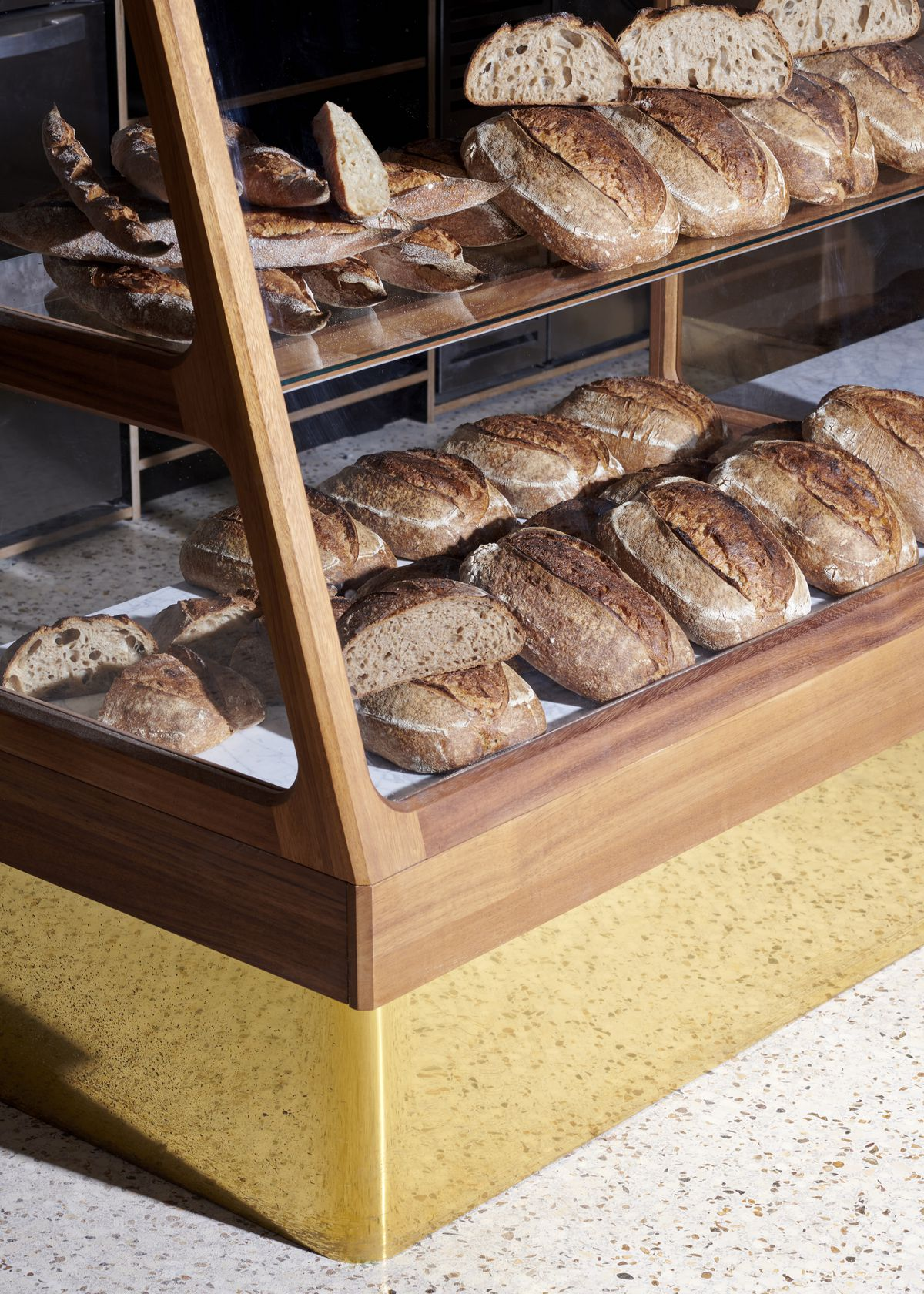 A European-style wooden case holds loaves of sourdough bread, with glass panels on the front.
