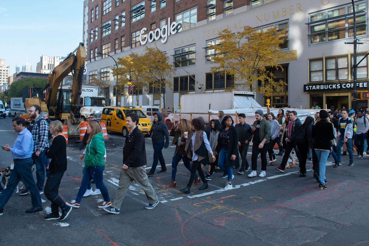 Google employees crossing the street in front of a Google building