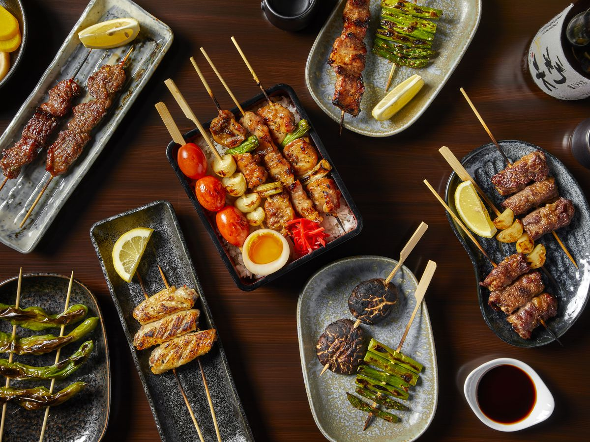 A table fileld with plates of grilled skewers