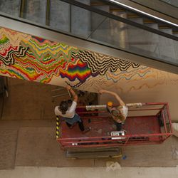 """Jen Stark hard at work on """"Drippy,"""" which wraps another elevator in the structure."""
