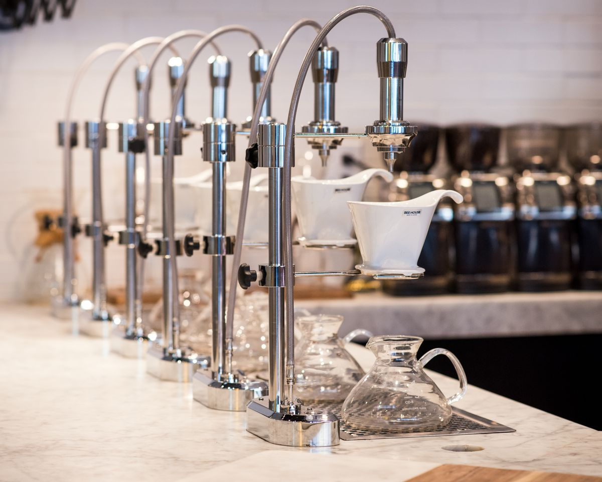 A line of five pour-over coffee machines.