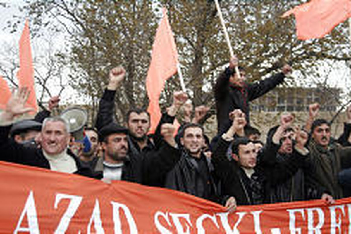 """Opposition protesters carry orange flags and shout """"Freedom!"""" during a rally in Baku, Azerbaijan, Saturday."""