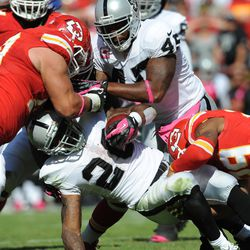 Oakland Raiders running back Darren McFadden (20) is tackled by Kansas City Chiefs defensive end Mike DeVito (70) and strong safety Eric Berry (29) during the second half at Arrowhead Stadium. The Chiefs won 24-7.