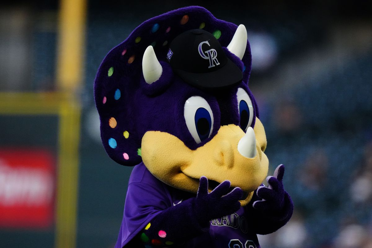 A head shot of Dinger, the Rockies mascot, with the area around the foul pole and like in the background, out of focus