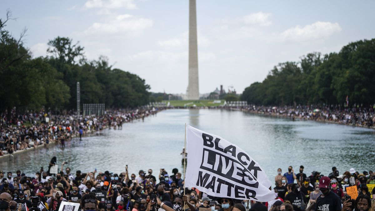 A Black Lives Matter flag flies in front of the Washington Monument, as the Washington, DC, National Mall is filled with protesters.
