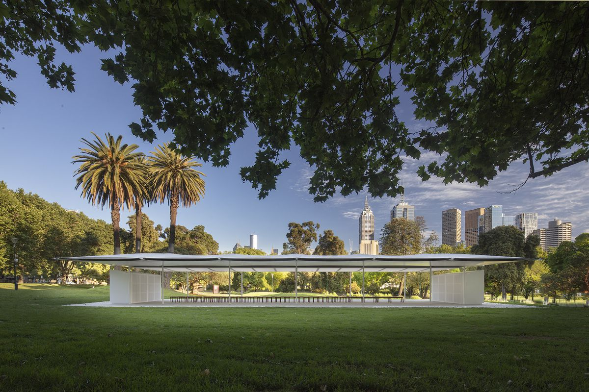 White pavilion surrounded by palm trees.