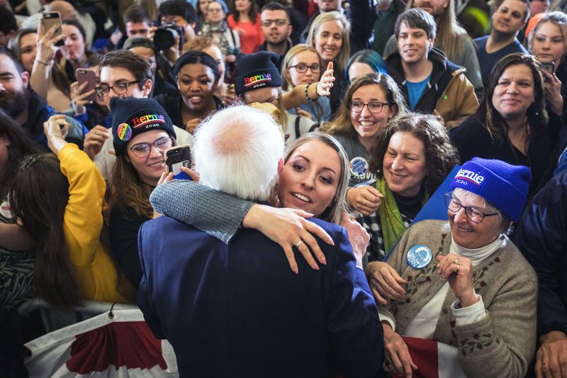 Bernie Sanders hugs a woman as a crowd looks on.