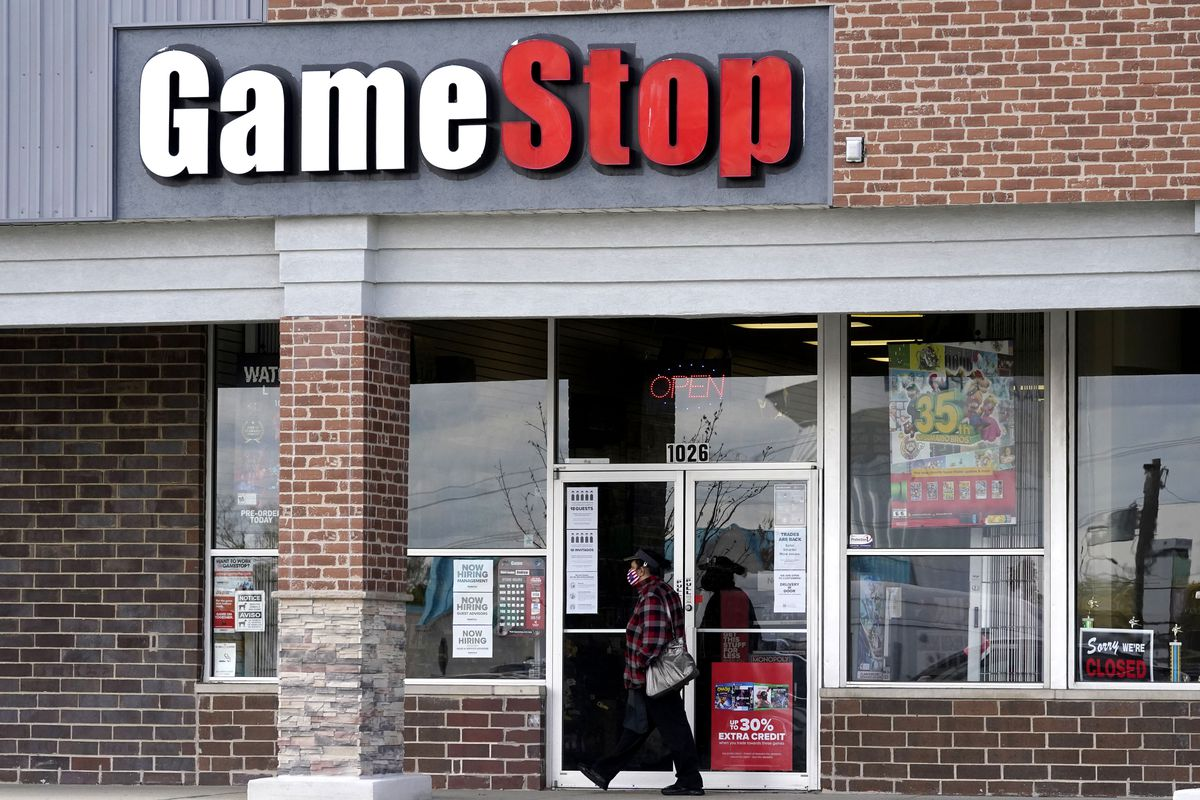 In this Oct. 15, 2020 file photo, a woman wears a face mask as she walks past a GameStop store in Des Plaines, Ill.