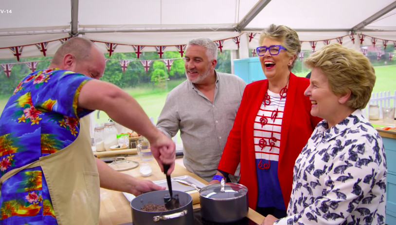 Prue Leith laughs while standing in between Paul Hollywood and Sandy Toksvig.
