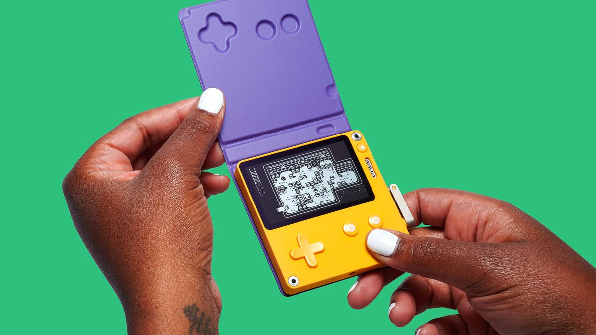 Close-up shot, two hands holding the Playdate handheld gaming device, flipping up its protective screen