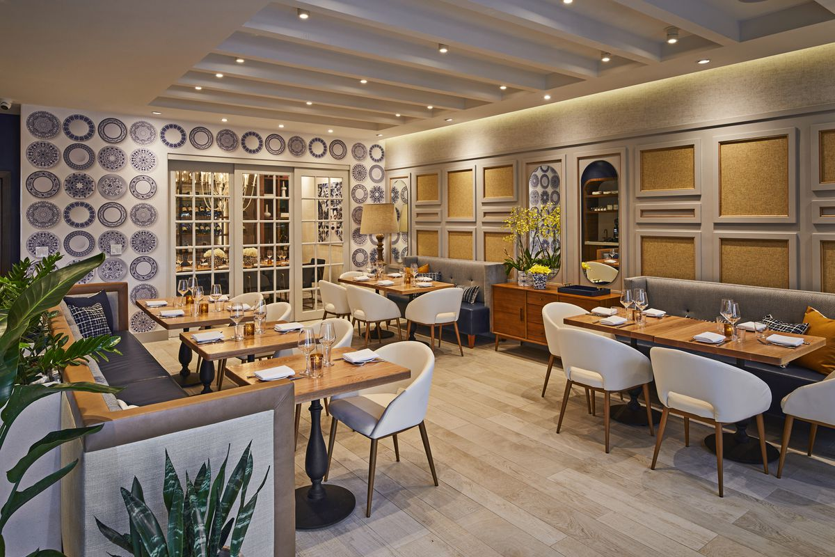 large dining room with bright wall decor and white chairs and brown tables