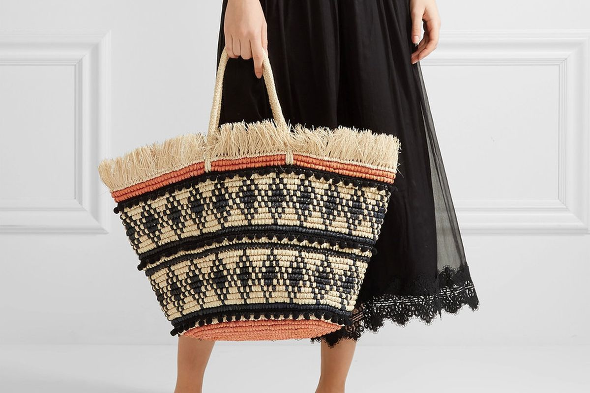 A model holding a woven straw tote