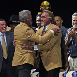 Brett Favre embraces Kevin Greene as Packers defensive coordinator Dom Capers looks on