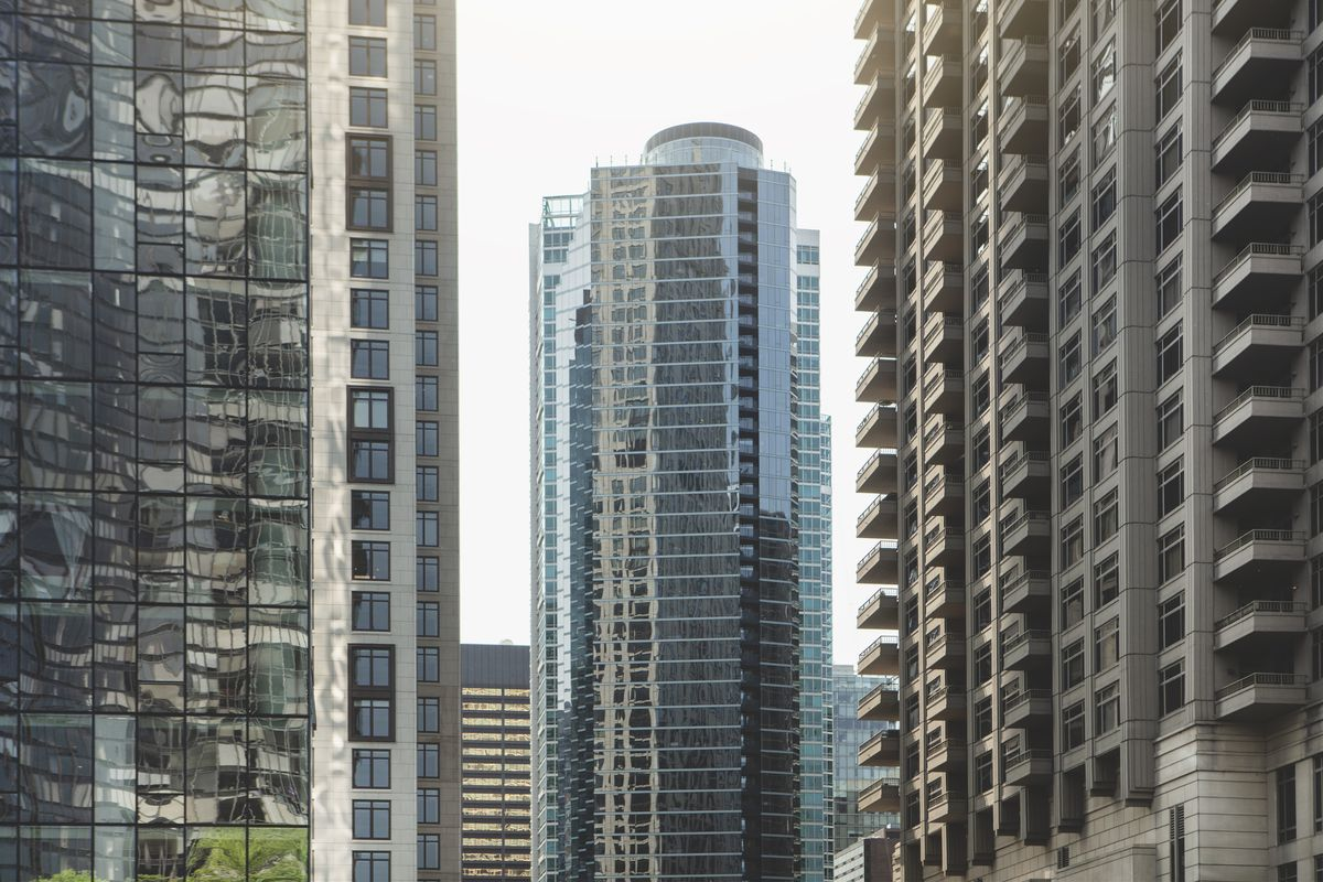 Two tall office and condo towers frame another glassy downtown building in Chicago.