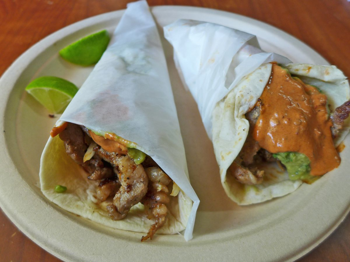 A pair of cone shaped tacos wrapped in white paper spilling out meat and orange sauce.
